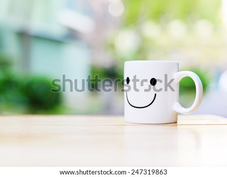 Happy cup on wood table. Concept about happiness and waiting for someone. - stock photo
