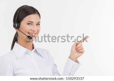 Happy customer service representative. Beautiful young female customer service representative in headset pointing away and looking at camera while isolated on white - stock photo