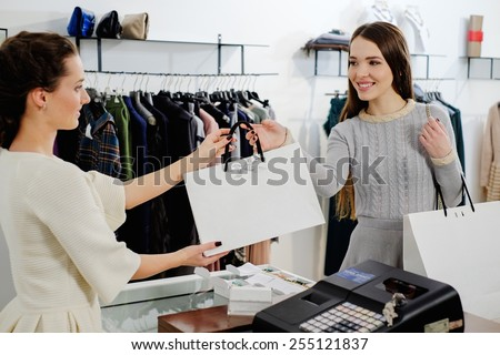 Happy customer with shopping bag in fashion showroom  - stock photo