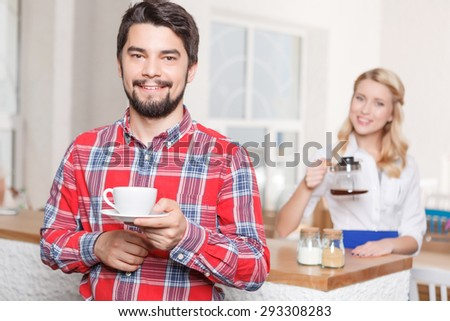 Happy customer. Young man with beard holding cup of coffee on background of waitress.  - stock photo