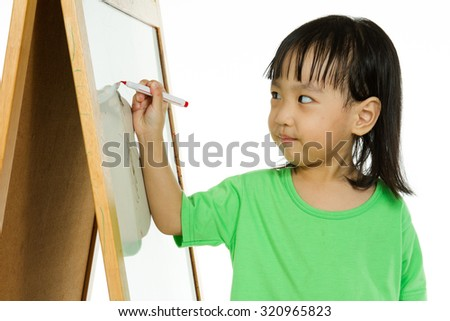 Happy cute Asian Chinese toddler girl drawing or writting with marker pen on a blank whiteboard at home, preschool, daycare or kindergarten in plain white isolated background. - stock photo