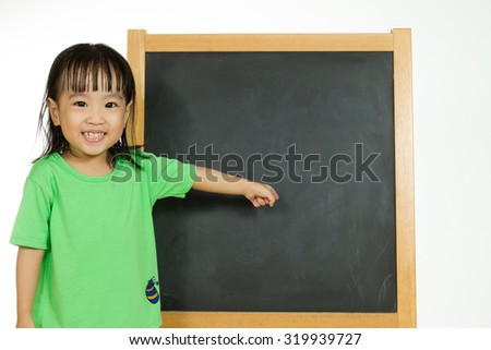 Happy cute Asian Chinese toddler girl standing beside a blank blackboard at home, preschool, daycare or kindergarten in plain white isolated background. - stock photo