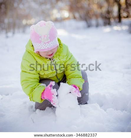 Happy cute baby girl in winter park - stock photo