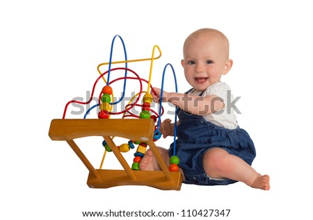 Happy cute baby playing on the floor with a wooden educational toy with looped wires for teaching coordination and colors isolated on white - stock photo