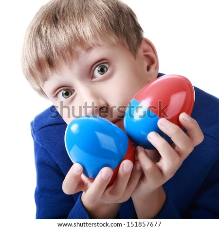 Happy cute blond boy in a blue sweater holds two colorful plastic eggs as an education concept  (isolated on white background)   - stock photo