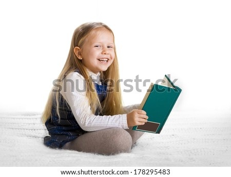 happy cute blonde haired school girl wearing a school uniform reading a book sitting on the bed - stock photo