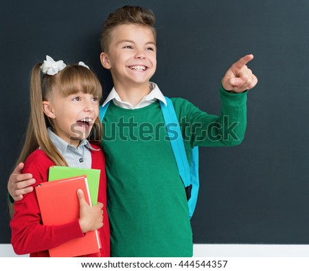 Happy cute boy and girl learning playfully in front of a big chalkboard  - stock photo