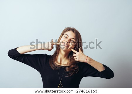 Happy cute brunette girl points a finger at the teeth - stock photo