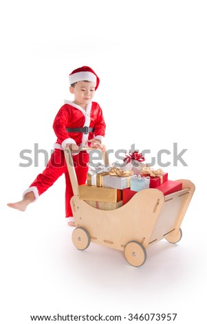Happy cute child boy in Santa hat pushing a trolley of colorful Christmas gift boxes, isolated on white background. - stock photo