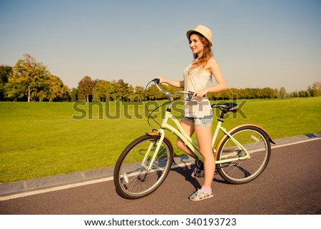 happy cute girl with bike walking on park - stock photo