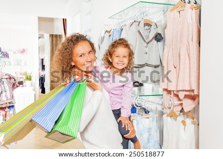 Happy cute girl with her mother holding bags - stock photo