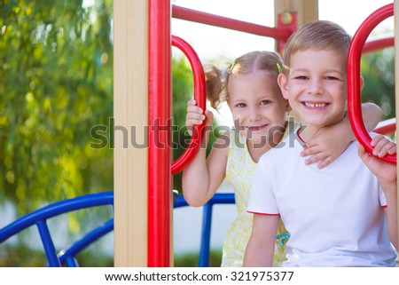 Happy cute kids having fun at playground - stock photo