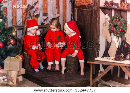 Happy cute little babies in Santa's costumes near Xmas tree - stock photo