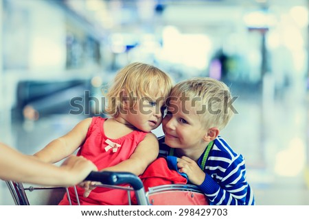Happy cute little girl and boy at airport riding on luggage cart - stock photo