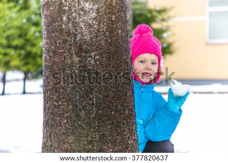 Happy, cute, little girl hiding behind the tree and will soon throw the snowball in yard in winter day - stock photo