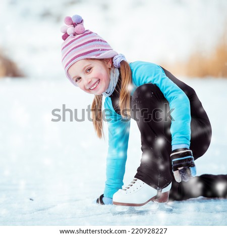 happy  cute little girl in thermal suits sits on the ice in winter outdoors - stock photo