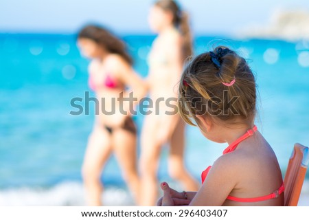 Happy cute little girl watching girls on beach vacation, tropical sea background. - stock photo