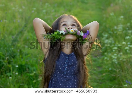 Happy cute little girl with long flowing hair and a wreath of wildflowers laughing on the summer meadow - stock photo