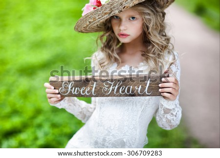 Happy cute little girls with long hair in long white dresseswith wooden plaque with text about love little bridesmaid  with bouquets  Beautiful Teenage Girl Having Fun in Autumn Park , focus on word heart - stock photo