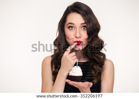 Happy cute lovely curly young woman with retro hairstyle holding birthday cupcake with candle on palm  - stock photo
