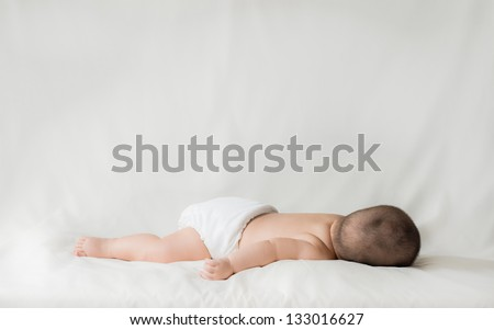 Happy cute 5 month old Asian baby boy with short black hair wearing a white cloth nappy and sleeping on his front on a white bed - stock photo