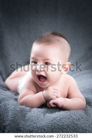 Happy cute 4 months old Asian baby boy with short black hair wearing a white cloth nappy and lying on his front on a white bed.Crawling beautiful baby boy - stock photo