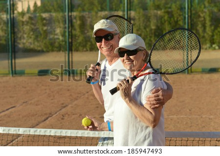 Happy cute senior couple playing tennis outdoors - stock photo