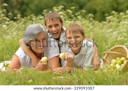 Happy cute smiling family on green summer grass with apples - stock photo