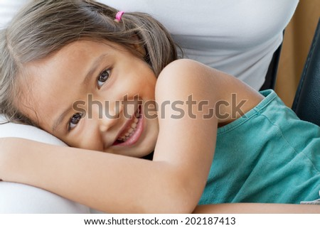happy, cute, smiling female child, daughter playing on her mother's lap - stock photo