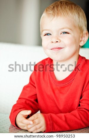 happy cute toddler boy with blue eyes and blond hair making faces - shallow depth of field, focus on the eyes - stock photo