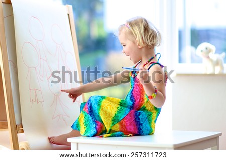 Happy cute toddler girl in colorful dress drawing family on paper using felt pen sitting next to window at home, preschool, daycare or kindergarten and enjoying art, artistic childhood concept - stock photo