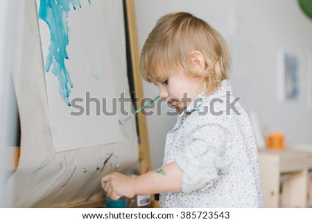 Happy cute toddler girl painting with gouache and watercolor paints indoors - stock photo