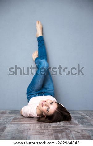 Happy cute woman lying on the floor with legs raised up  - stock photo
