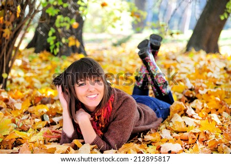 Happy cute woman outdoor portrait, lying in autumn park. - stock photo