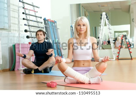 happy cutie athletic girl and guy,  execute exercise , in  sport-hall - stock photo