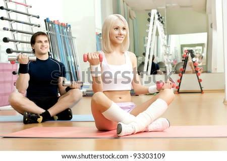happy cutie athletic girl and guy,  execute exercise with dumbbells and smile, in  sport-hall - stock photo
