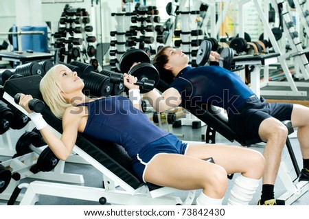 happy cutie athletic girl and guy,  lie exercise with dumbbells and smile, in  sport-hall - stock photo