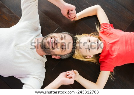 Happy dad and daughter. Top view of happy father and daughter holding hands and smiling at camera while lying on the hardwood floor together - stock photo