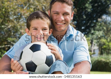 Happy dad and son with a football in a park smiling at camera - stock photo