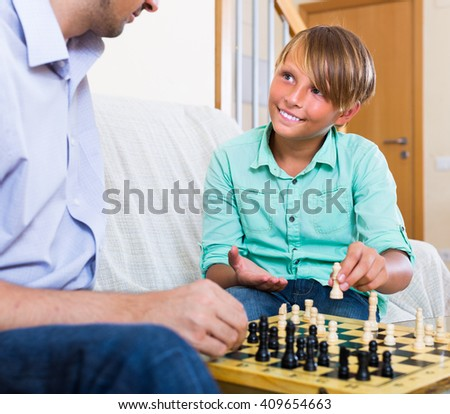 Happy dad and teenage son playing chess together at home - stock photo
