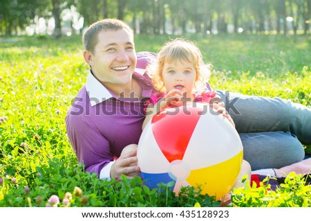 Happy dad with her daughter outdoors in sunlight - stock photo