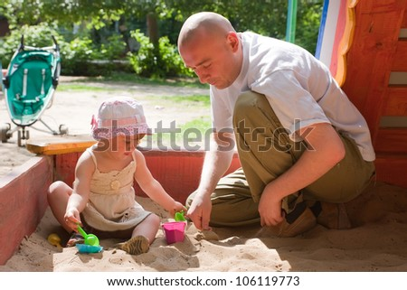happy dad with  toddler  playing with sand in sandbox - stock photo