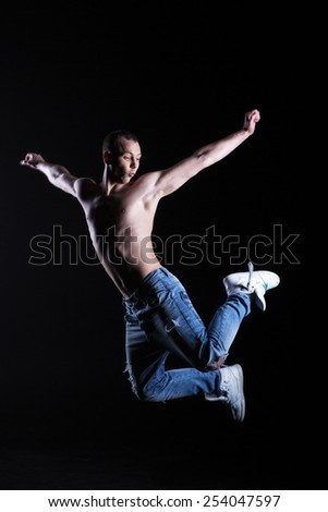 happy  dancer jumping on a black background - stock photo