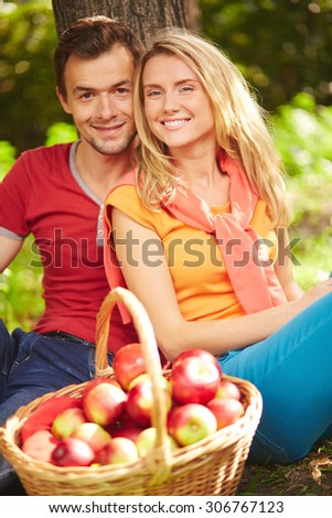 Happy dates with basket full of red apples sitting by tree and looking at camera - stock photo