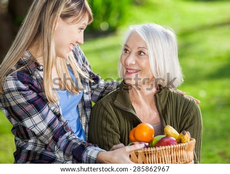 Happy daughter and mother looking at each other while holding fruit basket at campsite - stock photo