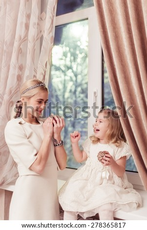 Happy daughter and mother over window - stock photo