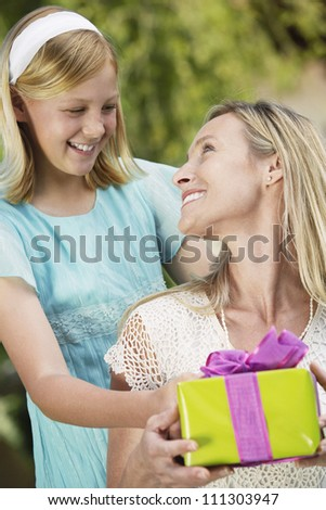Happy daughter giving present to mother at her birthday - stock photo