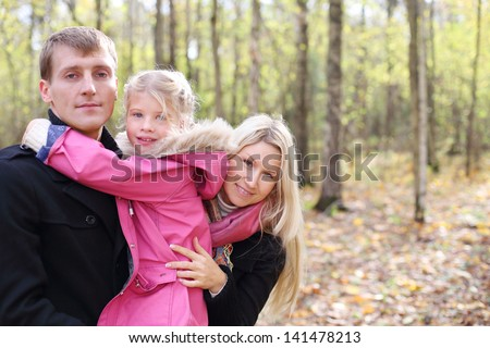 Happy daughter hugs father, and mother peeks out from behind them in autumn forest. Focus on mother. Shallow depth of field. - stock photo