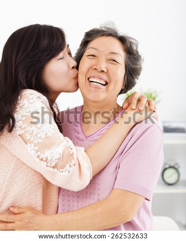 happy daughter kissing her mother - stock photo
