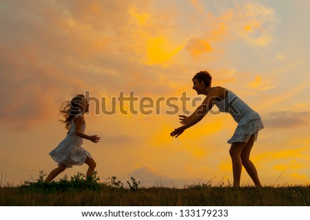 Happy daughter running to her mother on beautiful spring day. - stock photo